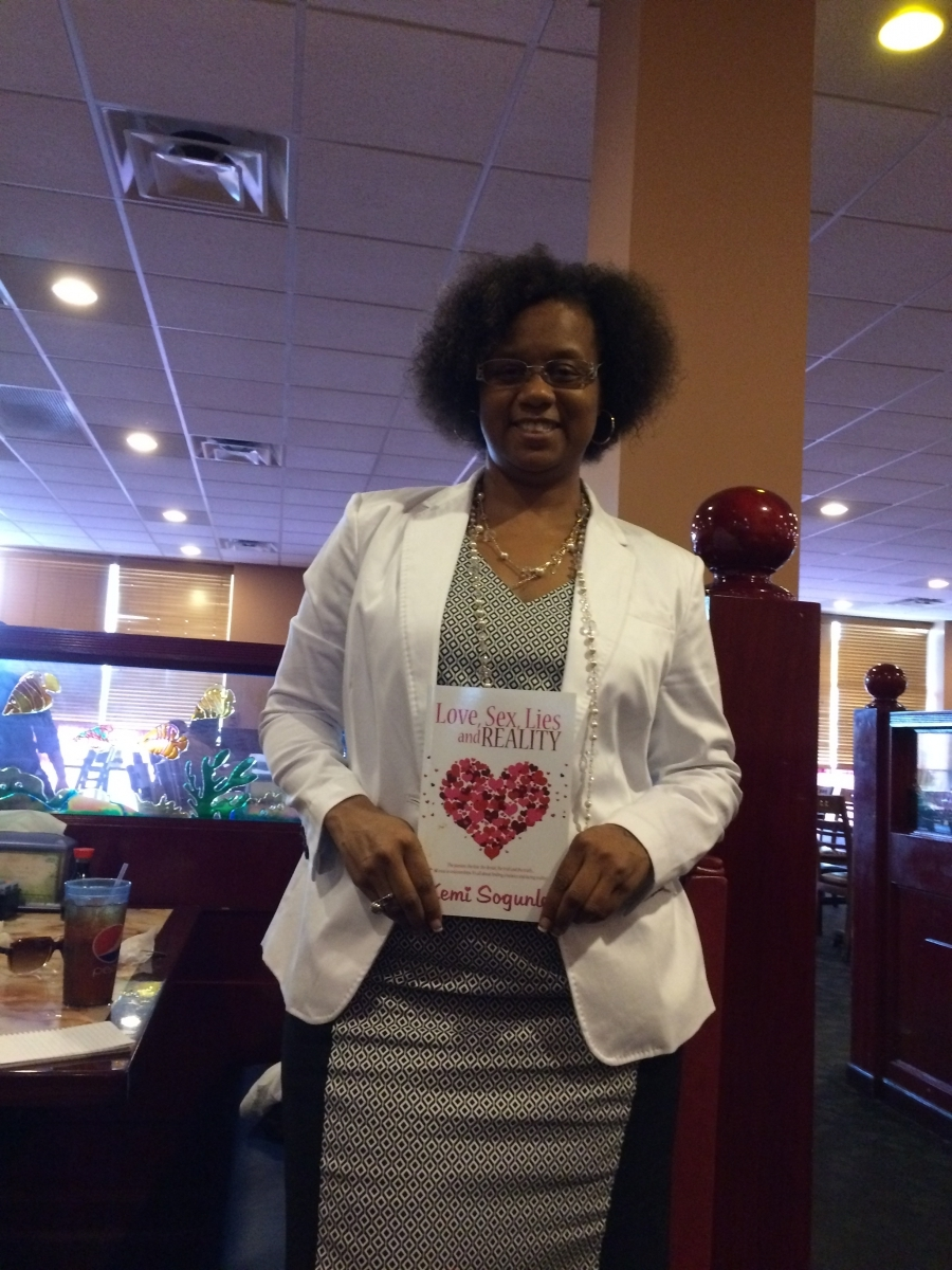 """Vicky Noland with a copy of Kemi's book, """"Love, Sex, Lies and Reality"""""""