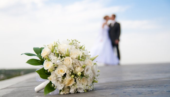 married couple with bouquet on the floor